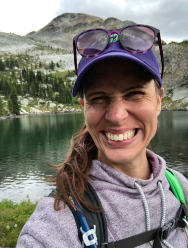 Picture of a woman in a purple hat standing in front of an alpine lake and smiling so hard her face hurts.